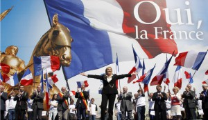 France's far right National Front political party leader Marine Le Pen waves on stage during her speech in front of the Opera following the National Front's annual May Day rally in Paris